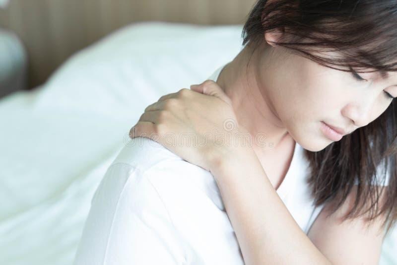 Hombro de la tenencia de la mano de la mujer del primer con dolor en cama, atención sanitaria y concepto médico imagen de archivo