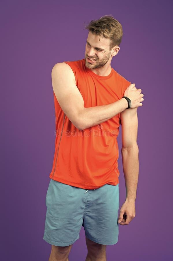 Hombro del tacto del deportista en el fondo violeta Dolor muscular de la sensación del hombre después de entrenar o del entrenami imágenes de archivo libres de regalías