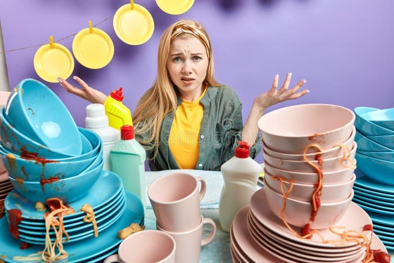 Hombros de encogimiento femeninos infelices que están tristes no sabiendo lavar los platos foto de archivo