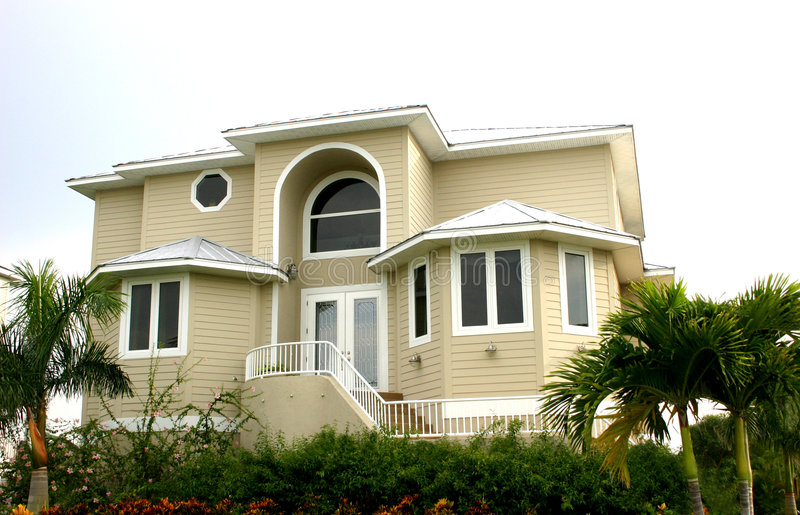 Home. Neat house in tropics, yellow with white trim, and surrounded by tropical landscaping stock photography