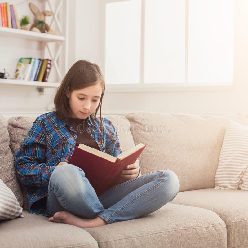 HOME acolhedor Menina pensativa nova com livro imagens de stock royalty free