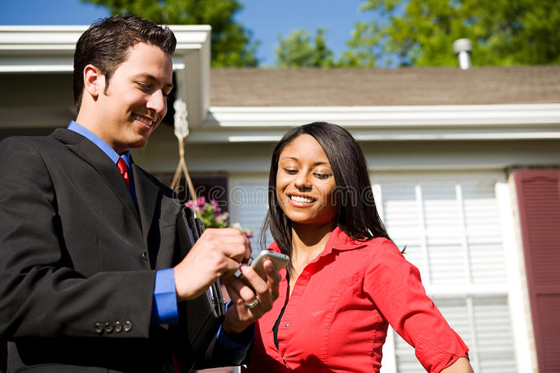 Home: Agent and Buyer Research Information. Extensive series of a Caucasian Real Estate Agent and African-American Couple in front of a home stock image