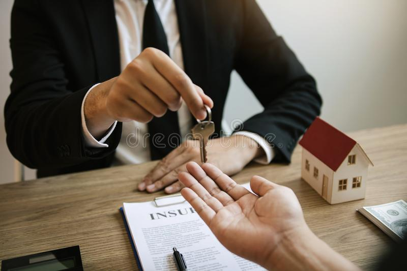 Home agents are handing out keys to home buyers who are signing contracts at the office.  royalty free stock photography