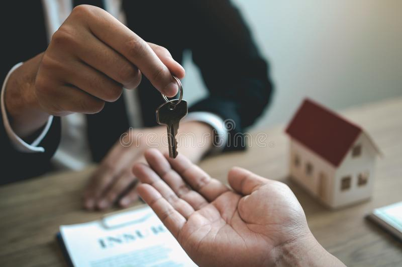 Home agents are handing out keys to home buyers who are signing contracts at the office.  stock photography