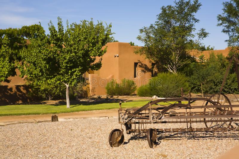 New Mexico Home with yard art. A home in Albuquerque, NM on a sunny day with grass gravel and old hay rake for yard art royalty free stock photo