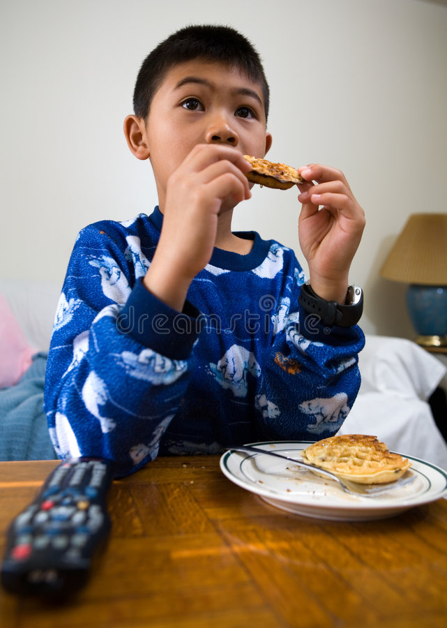 Home alone. Young asian boy eating waffles for breakfast while looking engrossed in the television stock images