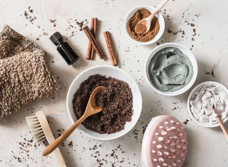 Home anti-cellulite products - coffee scrub, cosmetic clay, essential orange oil, hand anti-cellulite massager, nut scrub,. Cinnamon, natural loofah on a light stock image