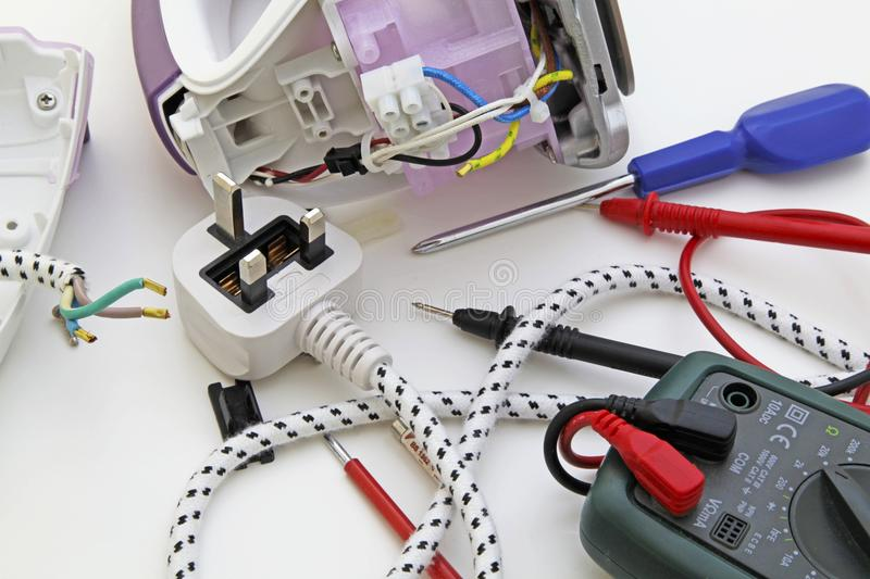 Home appliance fault finding. An appliance engineer repairing a domestic electric iron royalty free stock image