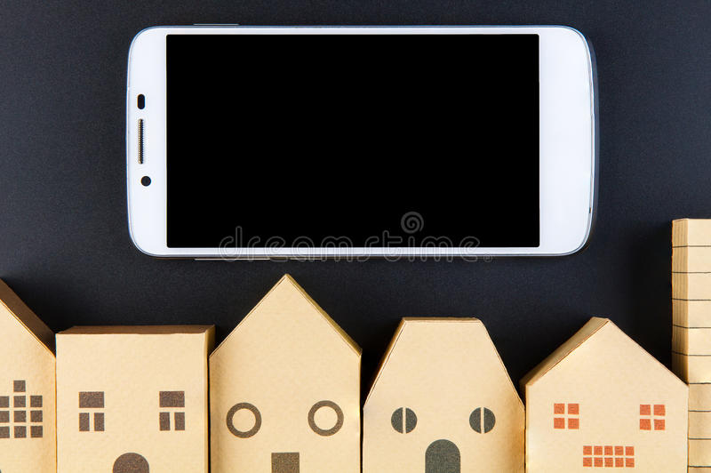 Home architectural model paper box cubes and smart phone on black background with copy space.Real estate concept. Home architectural model paper box cubes and royalty free stock image