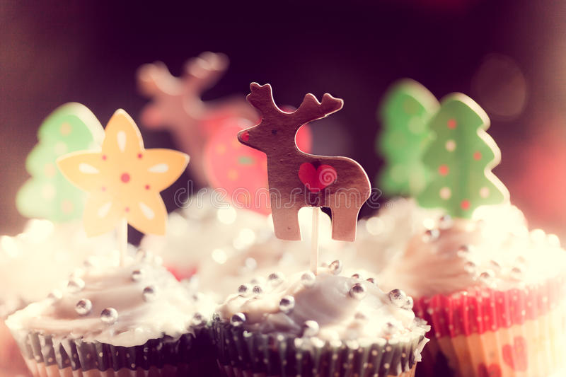 Home baked christmas cup cakes. Festive fairy cakes with silver sparkles and reindeers, stars and christmas tree decorations topping the silver frosted icing stock image