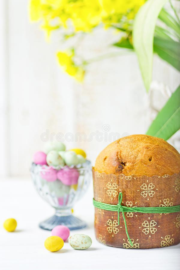 Home Baked Easter Sweet Cake Panettone in Paper Form Multicolored Speckled Chocolate Candy Eggs in Crystal Egg Cup on White Table stock images