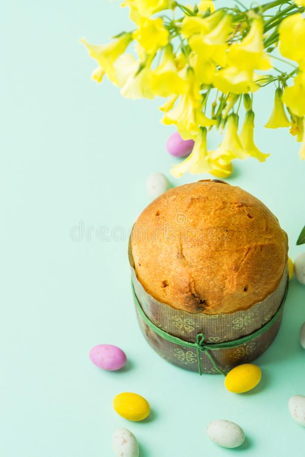 Home Baked Easter Sweet Cake Panettone in Paper Form Multicolored Speckled Chocolate Candy Eggs Scattered on Turquoise Background stock photos