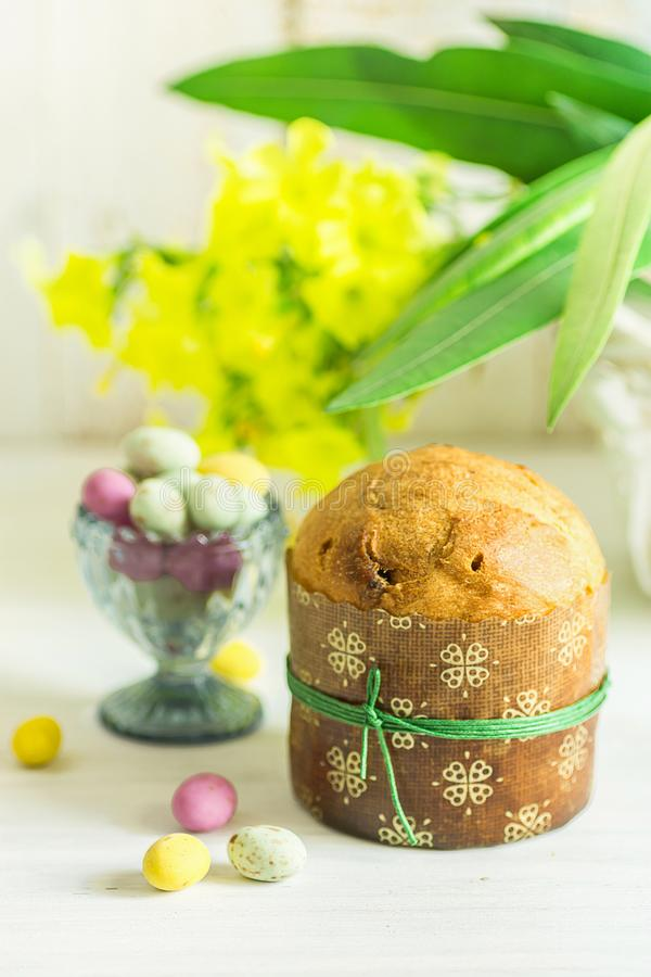 Home Baked Easter Sweet Cake Panettone in Paper Form Tied with Twine. Multicolored Speckled Chocolate Candy Eggs on Wood Table stock photo