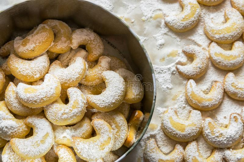 Home baked German Austrian traditional Christmas cookies vanilla crescents in tin box and on tray powdered with castor sugar. Holiday baking with kids sweet stock images