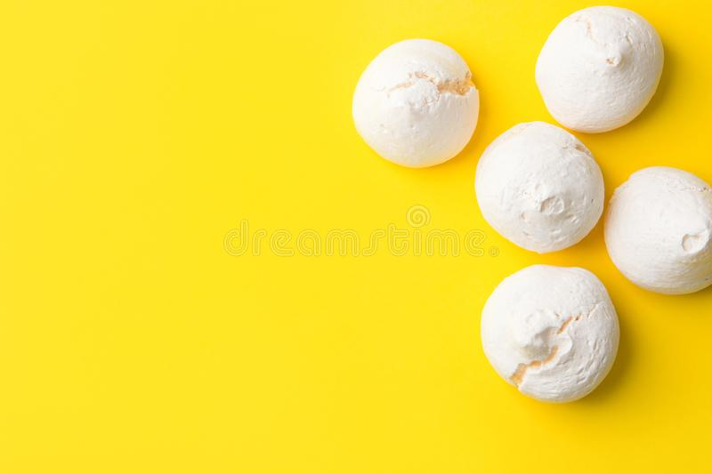 Home baked meringue cookies on bright yellow background. Minimalist flat lay. French Italian Swiss desserts cuisine confection. Airy elegant style. Recipe stock image