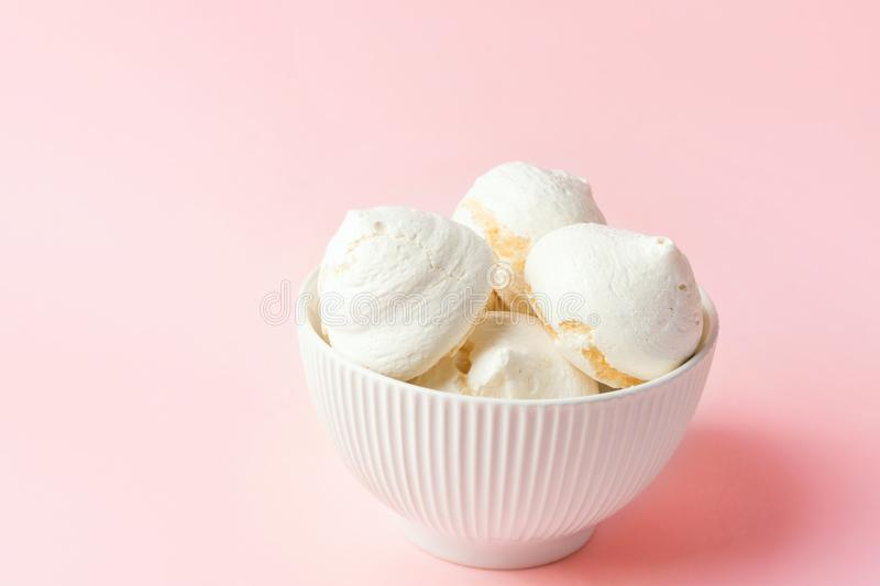 Home baked meringue cookies in white ceramic vintage bowl on gradient light pink background. French Italian Swiss cuisine desserts royalty free stock image