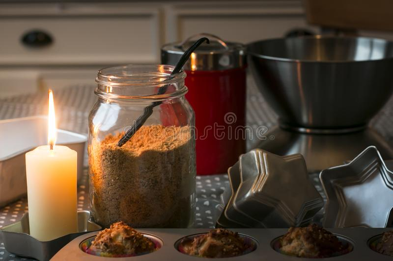 Home baking themed composition with muffins, brown sugar, glowing candle. Home baking themed composition with brown sugar, muffins in pan, star shaped molds and royalty free stock photos