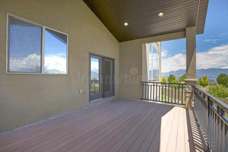 Home with balcony concrete exterior wall and round lights on the wooden ceiling. The cloudy blue sky, lake, and trees are reflected on the glass door and royalty free stock image