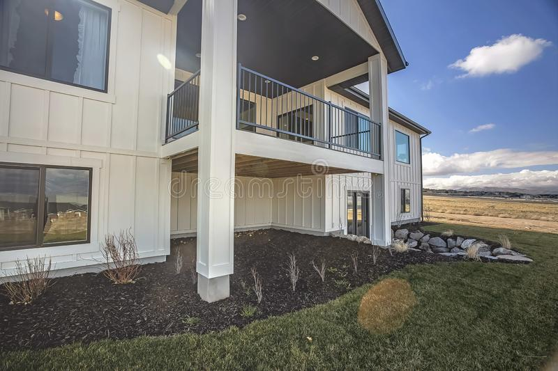 Home with a balcony extending beyond the white wooden exterior wall. The windows and doors reflect the cloudy blue sky and surrounding vast grassy terrain stock image