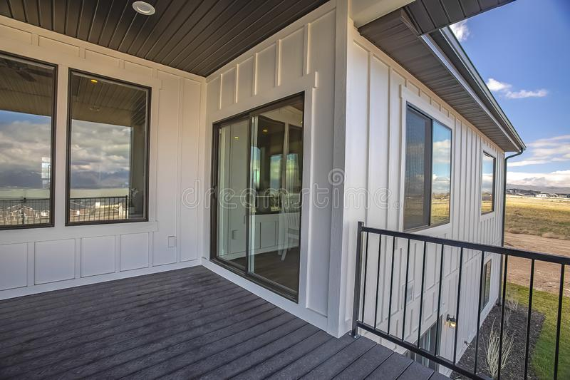 Home balcony with wooden floor metal railing and sliding glass access door. The scenic outdoor view is reflected on the shiny windows royalty free stock photography
