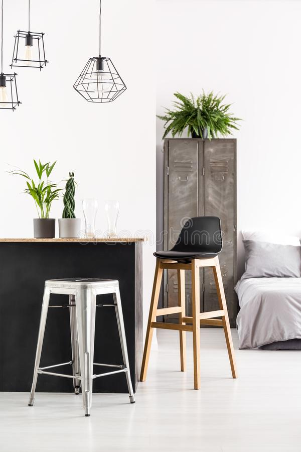 Home bar with plants. Handmade home bar with potted plants and beer glasses in white room interior with lamps and old locker stock image