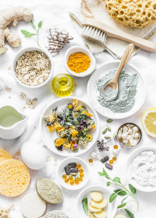 Home beauty products - clay, oatmeal, coconut oil, turmeric, lemon, scrub, dry flowers and herbs, sponges, soap, facial brush on l. Ight background, top view royalty free stock photo