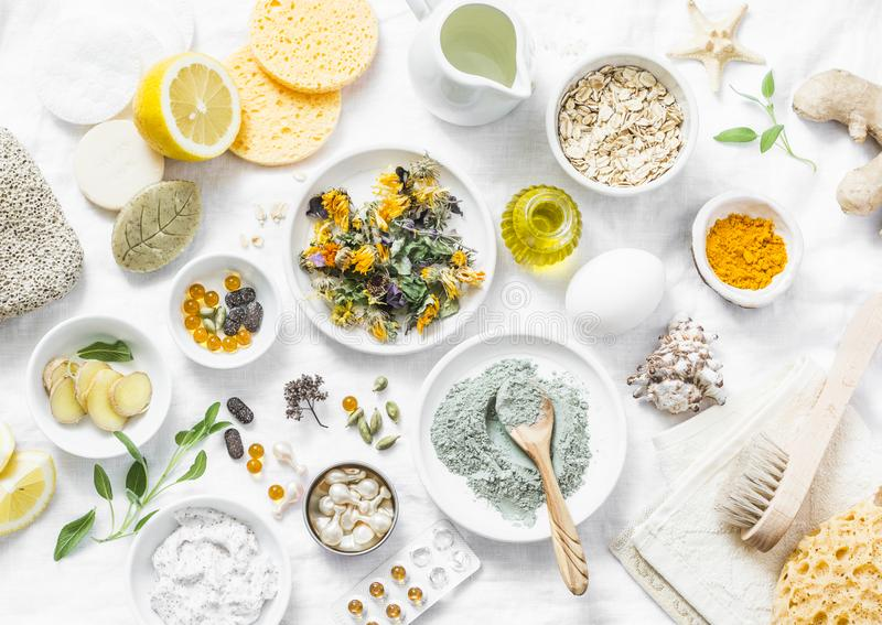 Home beauty products - clay, oatmeal, coconut oil, turmeric, lemon, scrub, dry flowers and herbs, sponges, soap, facial brush on l. Ight background, top view stock image