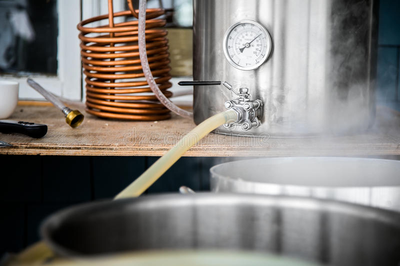 Home Brewing Kit and Pouring Craft Beer Wort into the Boil Kettle. stock image