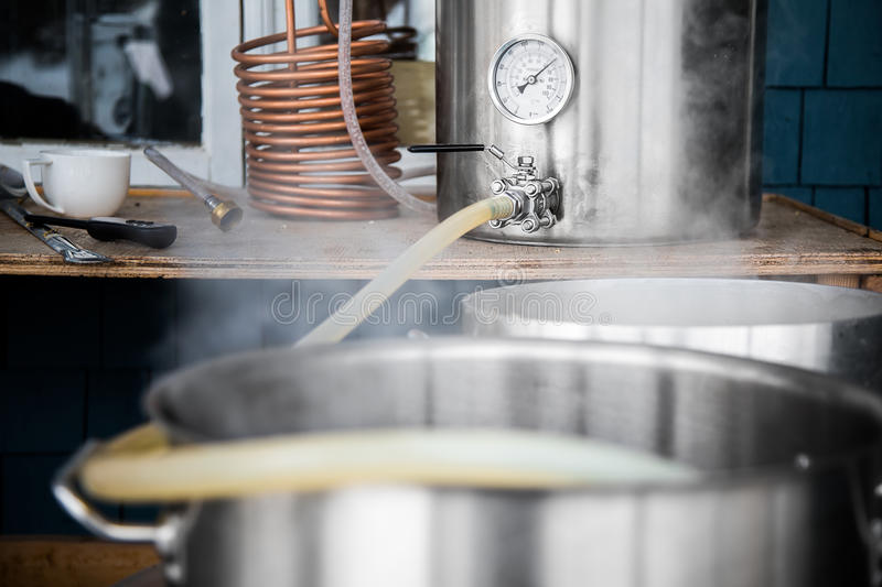 Home Brewing Kit and Pouring Craft Beer Wort into the Boil Kettle. Home Brewing Kit and Pouring Craft Beer Wort into the Boil Kettle with a Silicone Tube royalty free stock image