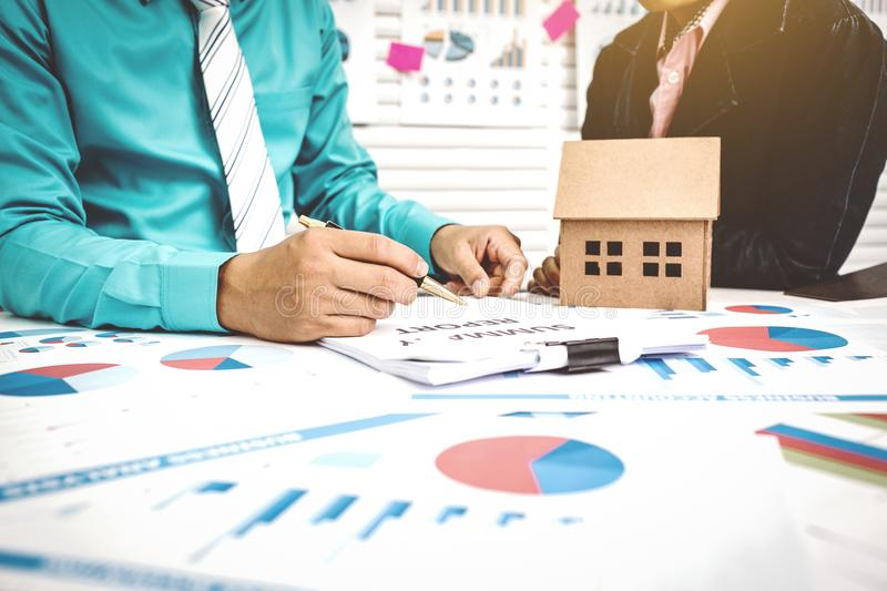 Signing of paper work home buying with broker and buyer. Home Brokerage offers home purchase paperwork and loans from the Government Housing Bank stock images