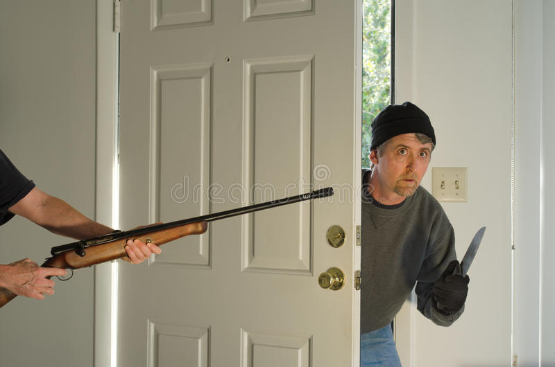 Home burglary thief being caught at gunpoint. A knife wielding home burglary thief is breaking into a home, but unbeknownst to the thief, the home owner is stock photos
