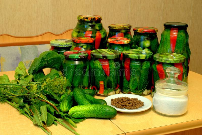 Home canned vegetables in glass jars and ingredients: cucumbers, pepper, salt, horseradish and dill. stock photo