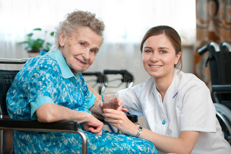 Home care. Senior women with her caregiver at home royalty free stock image