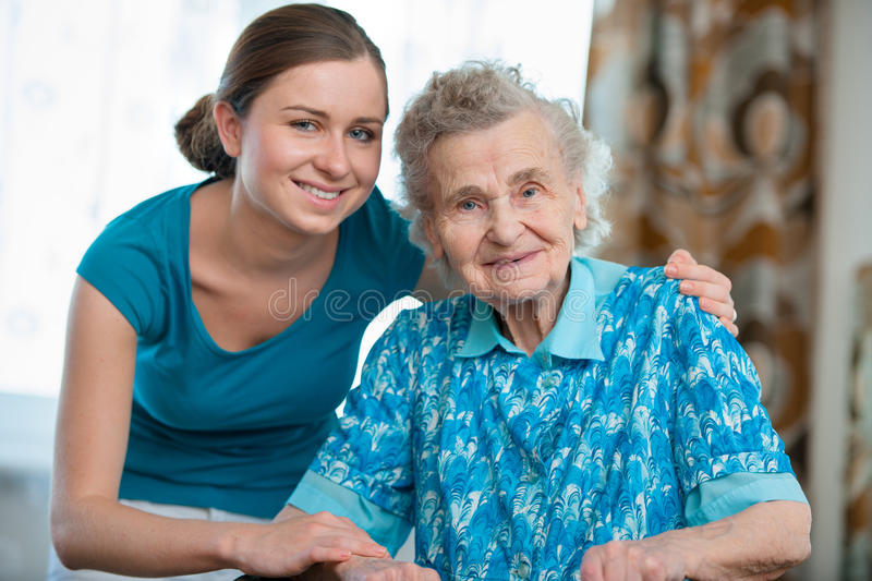 Home care. Senior women with her caregiver at home royalty free stock photography