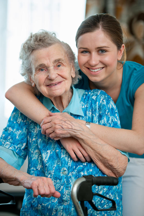 Home care. Senior women with her caregiver at home stock photography