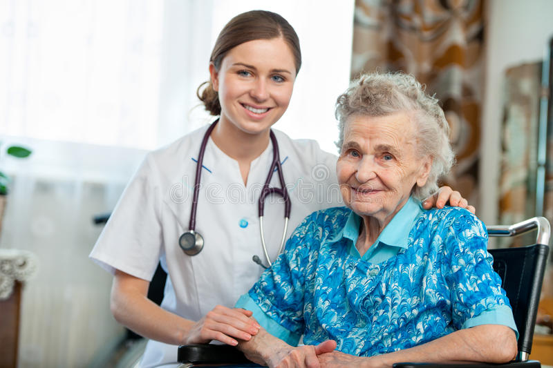 Home care. Senior women with her caregiver at home stock photo