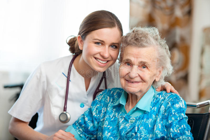 Home care. Senior women with her caregiver at home royalty free stock photos
