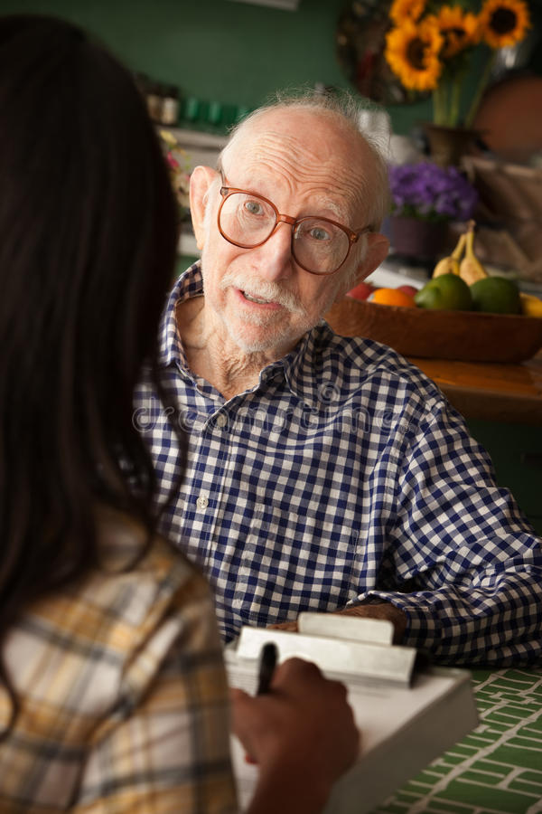 Home with care provider or survey taker. Elderly man in home with care provider or survey taker in kitchen stock photo