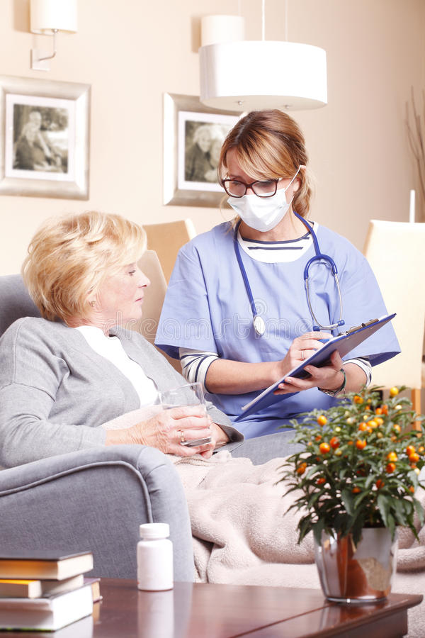 Home caregiver working. Portrait of home caregiver holding in her hand a clipboard and consulting with senior women while sitting at living room stock photography