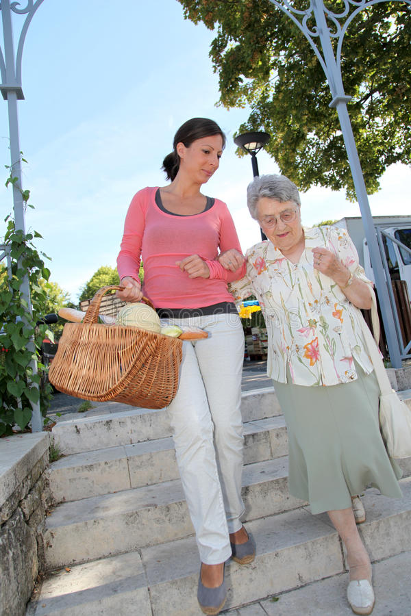 Home carer with elderly person in town royalty free stock photo
