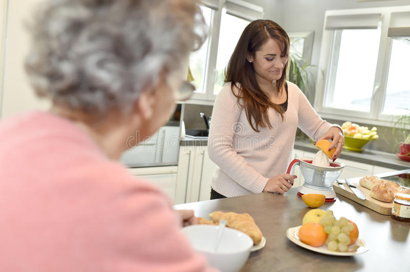 Home carer serving breakfast to a senior woman. Home helper serving breakfast to elderly woman royalty free stock photography