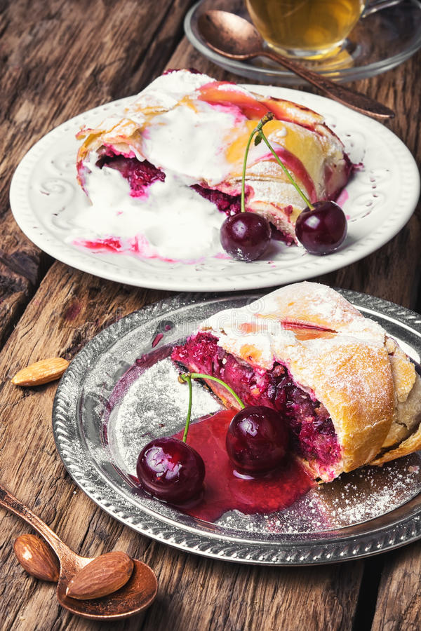 Home cherry strudel. Traditional puff pastry strudel with berries of cherry stock photo