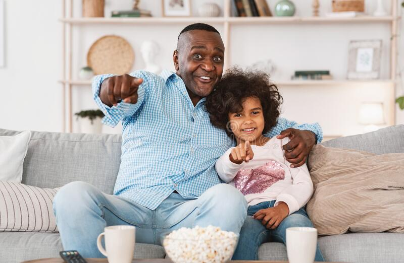 Home cinema. African American family of grandfather and grandchild watching television together indoors. Home cinema concept. African American family of stock photo