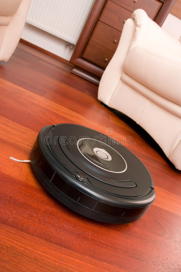 Home cleaning robot. Close-up home vacuum cleaning robot in action on genuine living room wooden floor. Selective focus on robot stock photos