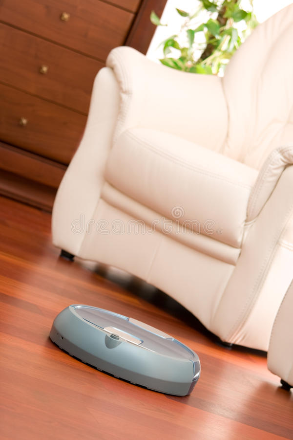 Home cleaning robot. Home washing robot in cleaning action on genuine living room wooden floor. Selective focus on robot stock photography