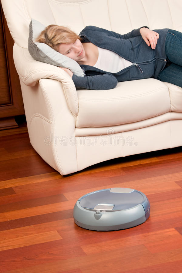 Home cleaning robot. Woman looking at home washing robot in cleaning action, saving her time. Genuine living room wooden floor (jatoba). Selective focus on robot royalty free stock photo