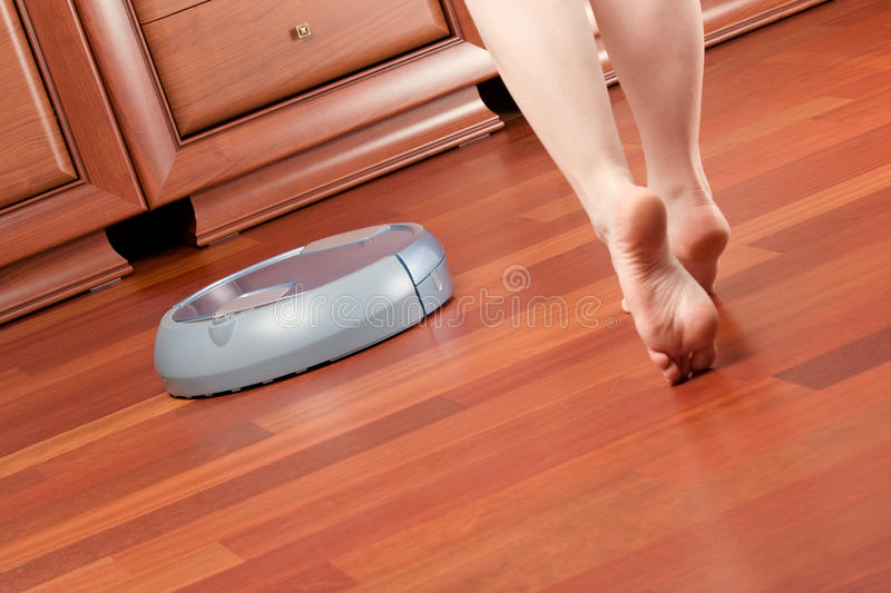 Home cleaning robot. Woman go round home washing robot in cleaning action, saving her time. Genuine living room wooden floor (jatoba). Selective focus on robot stock photography