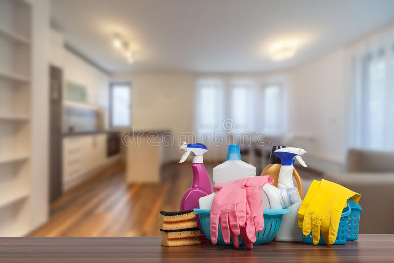 Home cleaning service concept with supplies. Close up of cleaning supplies in front of livingroom. Home cleaning service concept with supplies. Cleaning stock photography