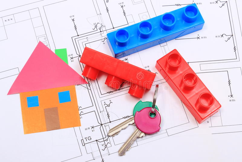 Home of colored paper, keys and building blocks on drawing of house. House of colored paper, home keys and plastic building blocks on construction drawing of stock photography
