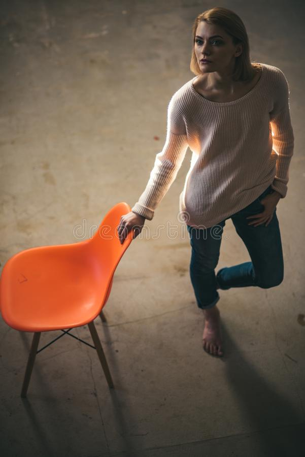 Home comfort with girl at chair. thoughtful woman at home with orange chair. lazy day at home. Frustrated woman standing. And looking away up. feeling hopeless stock photos